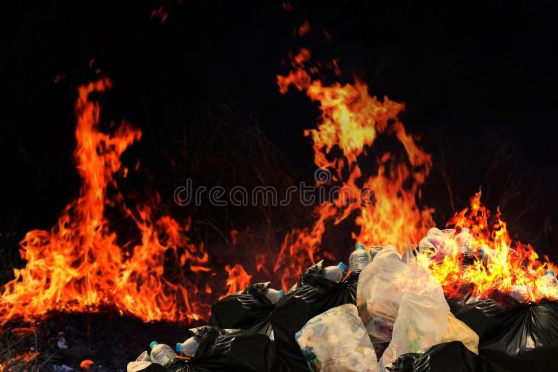 Brennen Sie viel überschüssigen Plastikabfall, die Mülltonnestapel Dump-Lose des Krams verunreinigend mit brennendem Plastikhaufe stockfoto