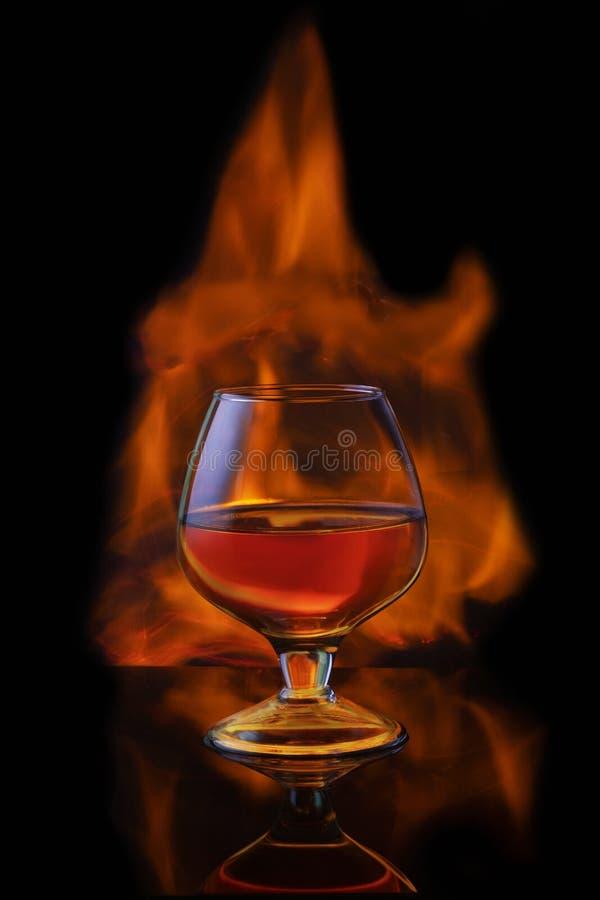 Brennende alkoholische Getränke mit Eiswürfeln, auf schwarzem Hintergrund lizenzfreie stockfotos