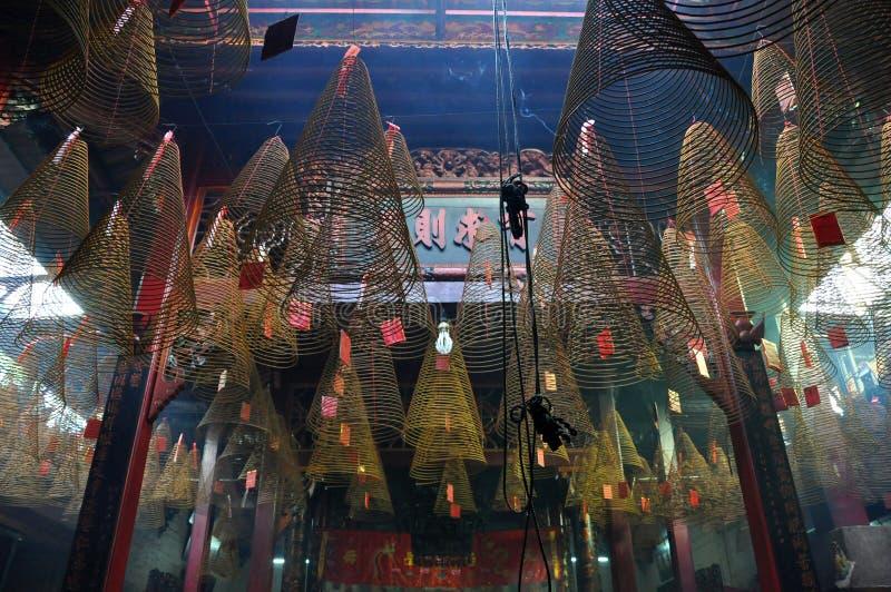 Brennende gewundene Räucherstäbchen, die von der Decke eines pago hängen stockbilder