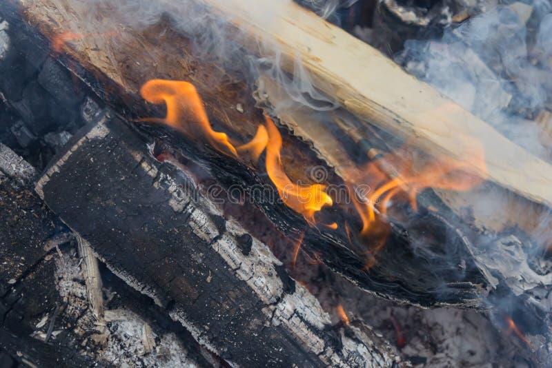 Brennende hölzerne Billets, Flammen und Rauch stockfoto