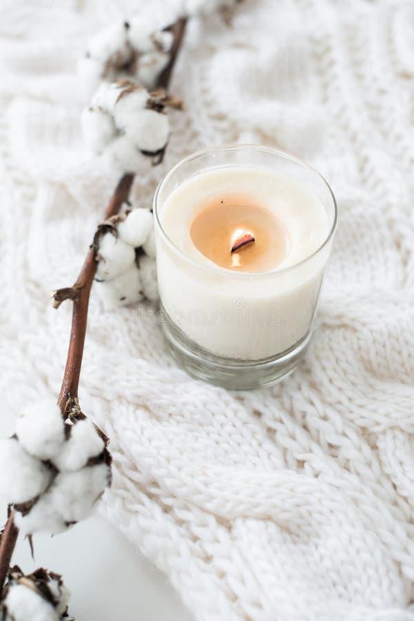 Brennende handgemachte Kerze mit Baumwollniederlassung auf weißem gemütlichem Winter stockfotos