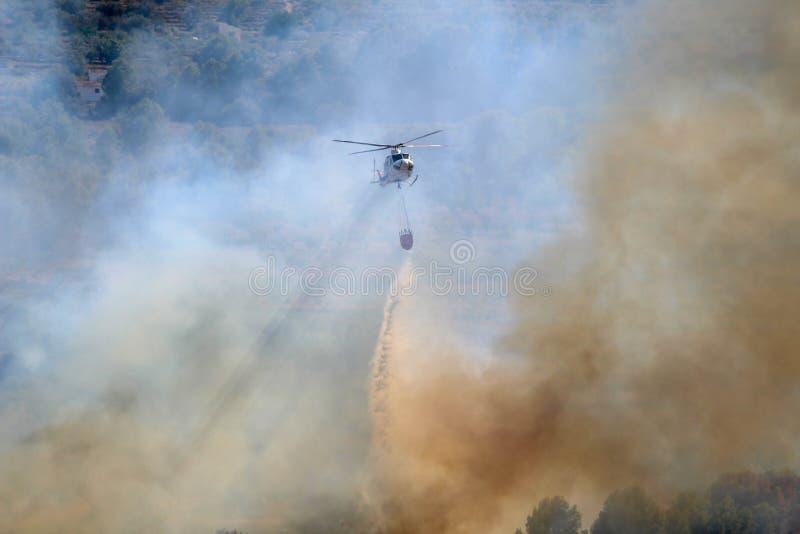 Brennende Hubschrauber des verheerenden Feuers, die heraus Feuer setzen stockfotos