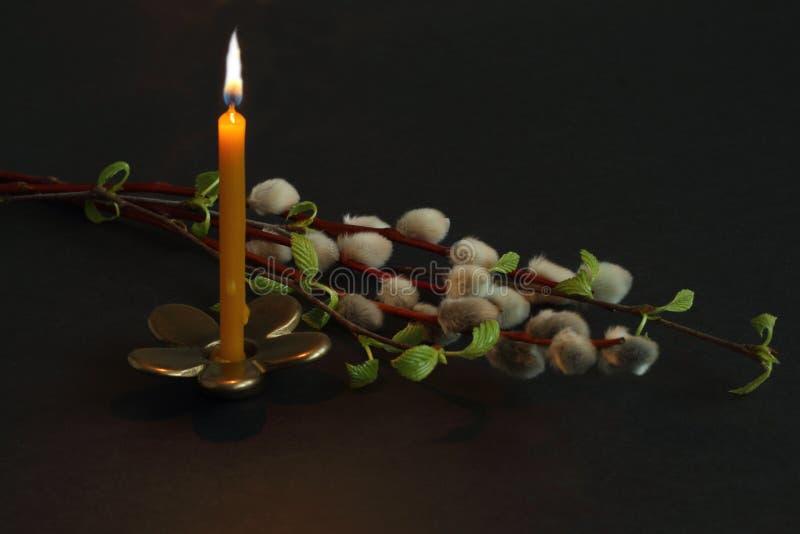 Brennende Kerze auf Bronzekerzenständer in Form des Blumen- und Weiden- und Birkenzweigs auf dunklem Hintergrund Symbolisches Kon stockbilder
