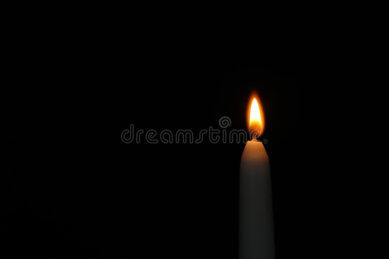 Brennende Kerze auf dunklem Hintergrund, Raum für Text Symbol stockfotografie
