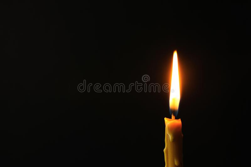 Brennende Kerze auf dunklem Hintergrund, Raum für Text Symbol stockbild