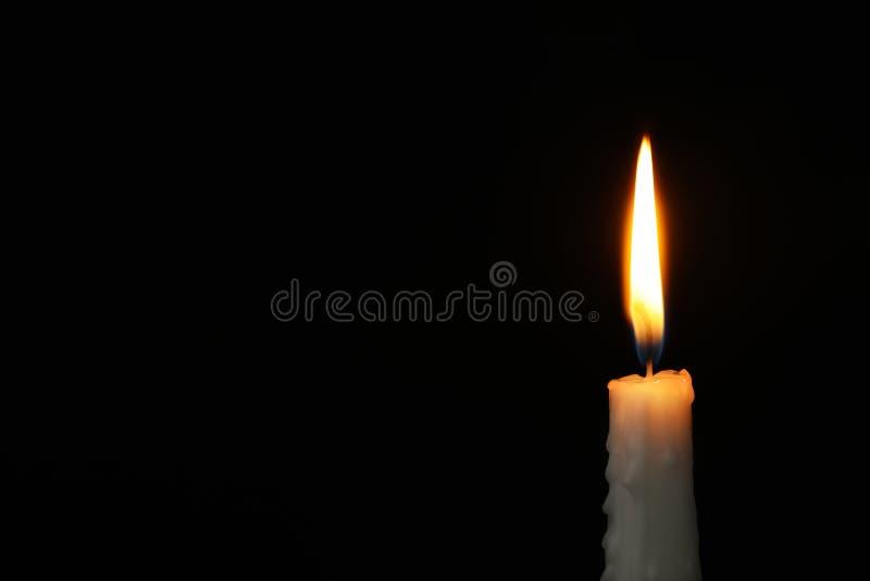 Brennende Kerze auf dunklem Hintergrund, Raum für Text Symbol lizenzfreies stockfoto