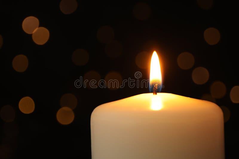 Brennende Kerze auf schwarzem Hintergrund mit unscharfen Lichtern, Raum für lizenzfreie stockbilder