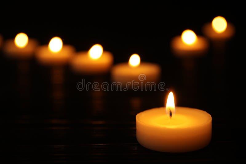 Brennende Kerze auf schwarzer Tabelle gegen verwischt, Raum für Text lizenzfreie stockfotografie