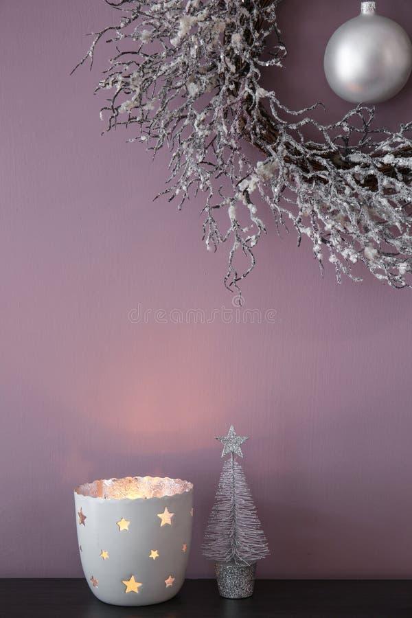 Brennende Kerze auf Tabelle mit dem Weihnachtskranz, der an der Farbwand hängt lizenzfreie stockfotografie