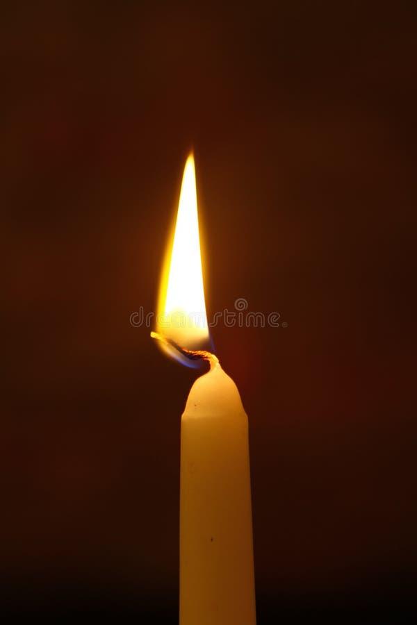 Brennende Kerze des kleinen Paraffins mit klarer Flamme auf dem starken schwarzen Hintergrund stockfotos