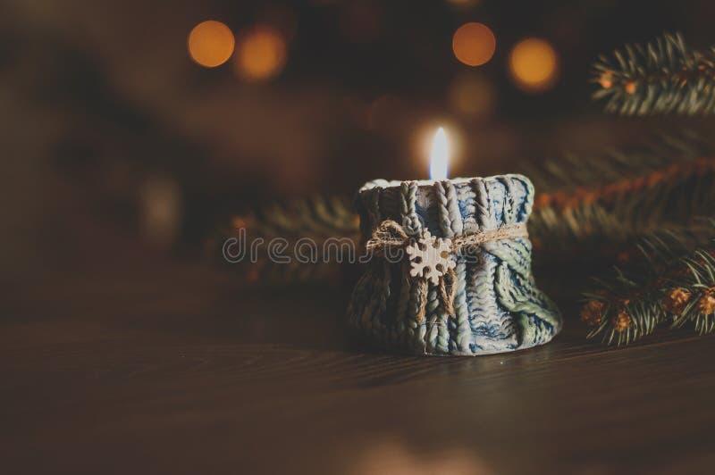 Brennende Kerze in einem gemütlichen blauen Kerzenständer mit einer Schneeflocke auf Th lizenzfreie stockfotografie