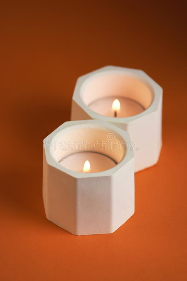 brennende Kerze in einem konkreten Kerzenhalter auf orange Hintergrund Abschluss oben lizenzfreies stockfoto