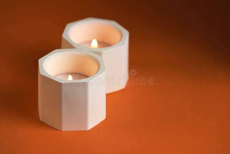 brennende Kerze in einem konkreten Kerzenhalter auf orange Hintergrund Abschluss oben stockfotos