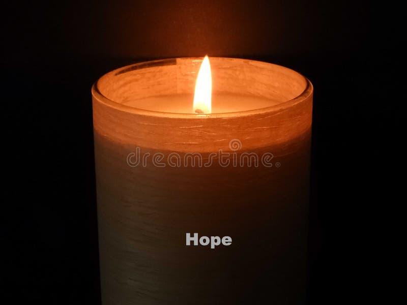 Brennende Kerze Hoffnung gegen einen schwarzen Hintergrund lizenzfreie stockfotos
