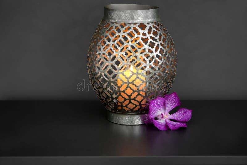 Brennende Kerze im dekorativen Halter mit Blume auf dunkler Tabelle stockbilder