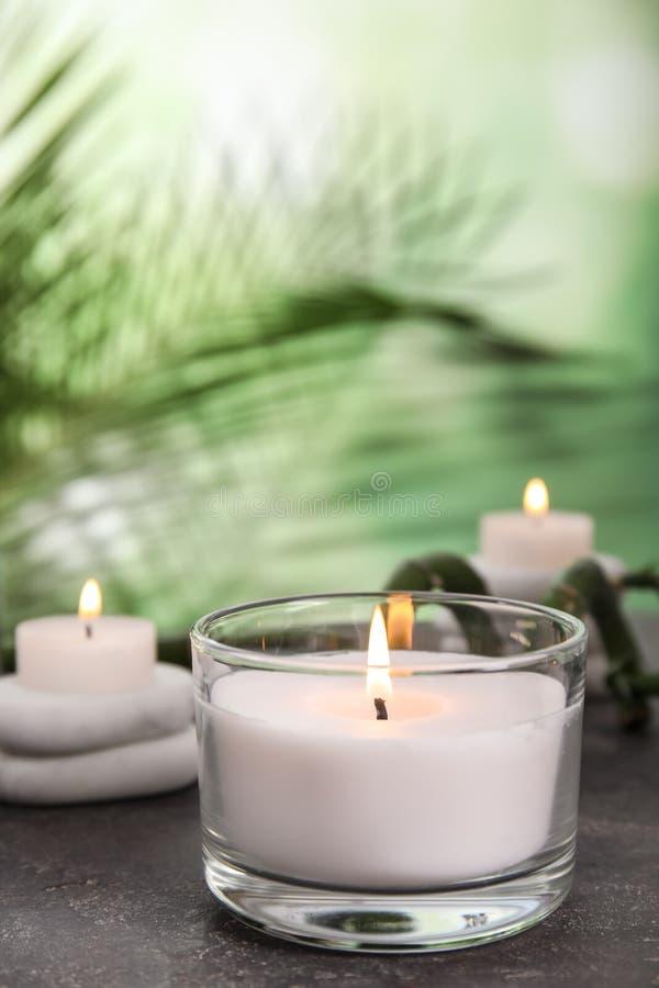 Brennende Kerze im Glashalter auf grauer Tabelle gegen unscharfen grünen Hintergrund lizenzfreie stockfotos