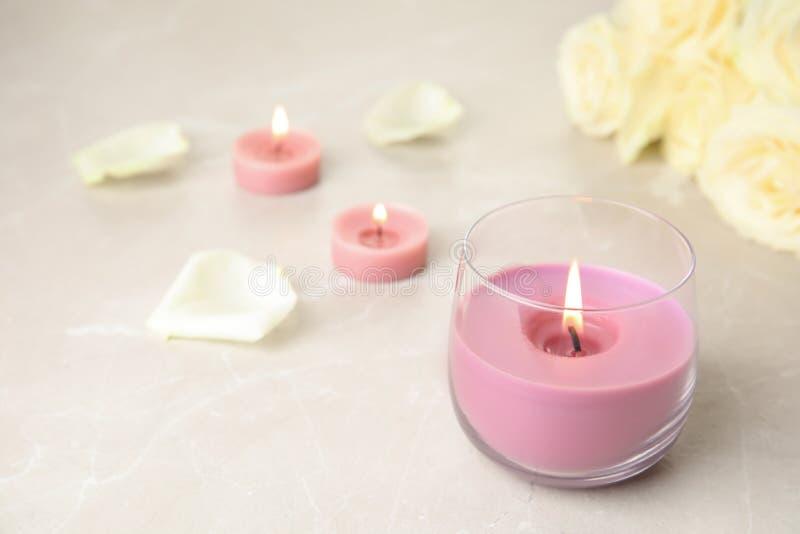 Brennende Kerze im Glashalter und in den Rosen auf Leuchtpult lizenzfreies stockbild