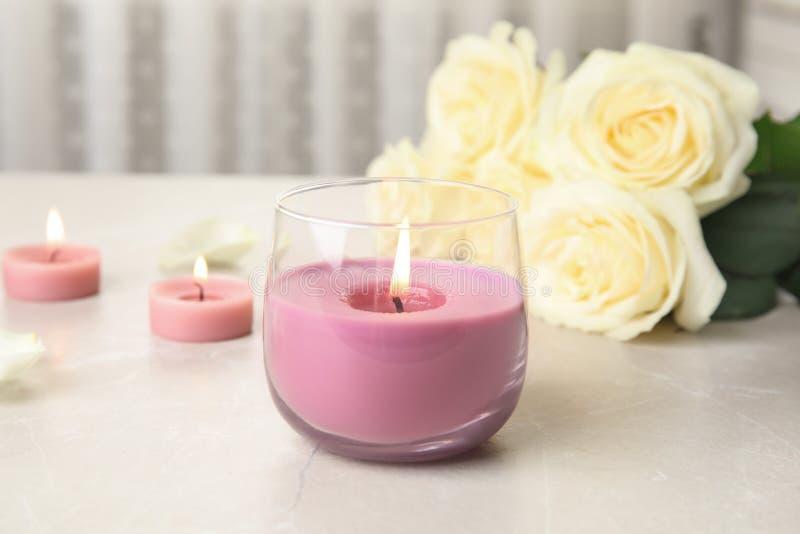 Brennende Kerze im Glashalter und in den Rosen auf Licht lizenzfreies stockbild