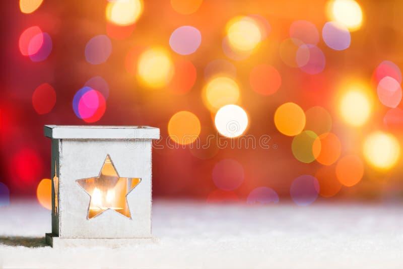 Brennende Kerze, im Schnee, mit defocussed feenhaften Lichtern, boke im Hintergrund, festlicher Weihnachtshintergrund stockfoto