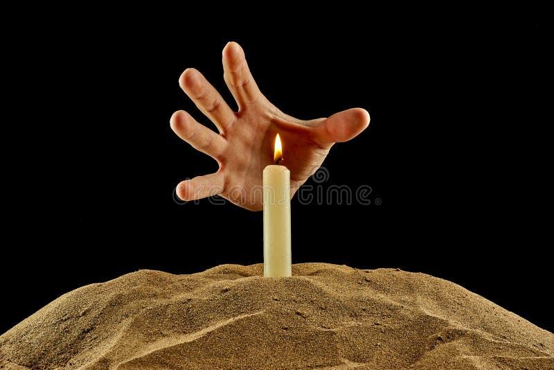 Brennende Kerze und Hand auf einem schwarzen Hintergrund stockfotos