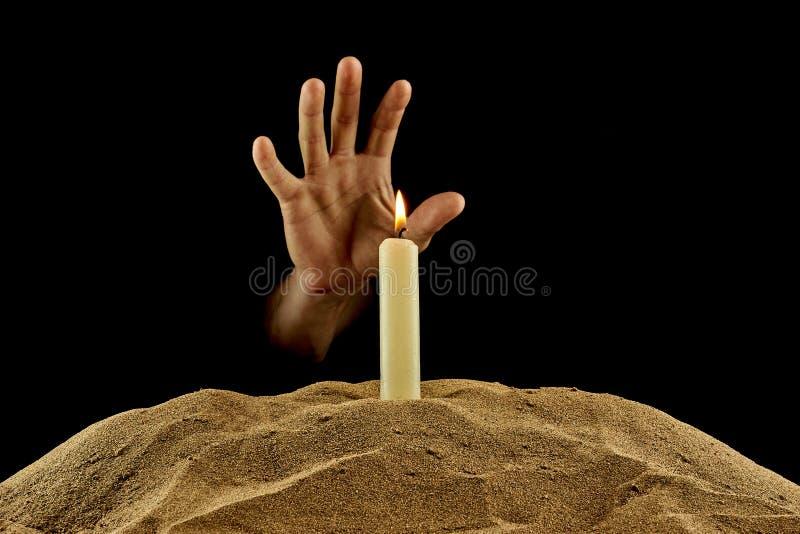 Brennende Kerze und Hand auf einem schwarzen Hintergrund stockfoto