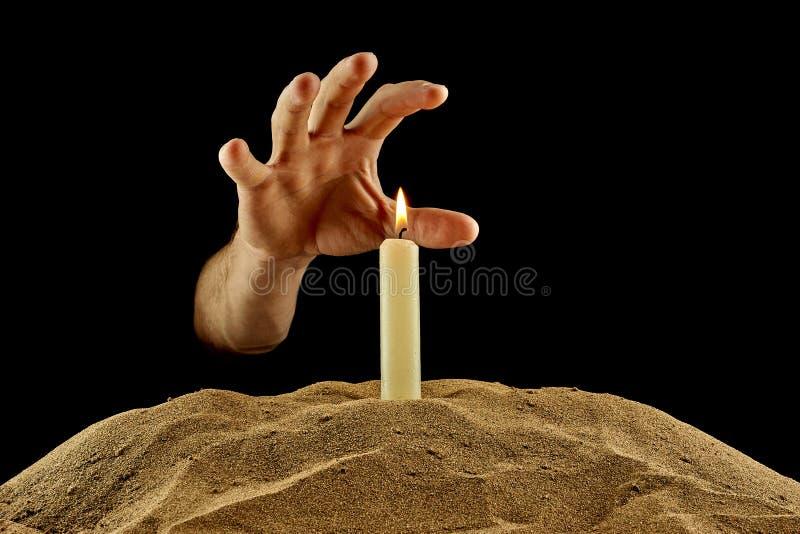 Brennende Kerze und Hand auf einem schwarzen Hintergrund lizenzfreies stockfoto