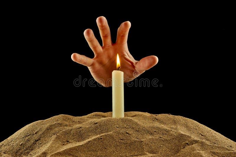 Brennende Kerze und Hand auf einem schwarzen Hintergrund lizenzfreies stockbild