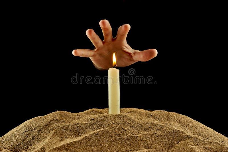 Brennende Kerze und Hand auf einem schwarzen Hintergrund stockbild