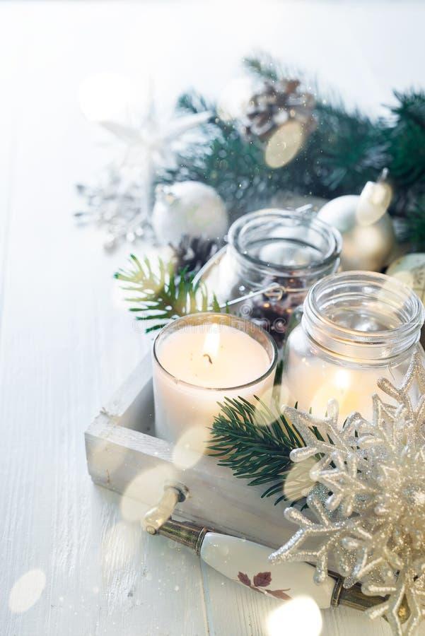 Brennende Kerze und Weihnachtsdekoration über Schnee und hölzerner Hintergrund, eleganter zurückhaltender Schuss mit festlicher S stockbilder