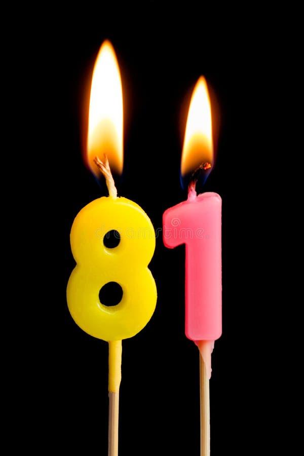 Brennende Kerzen in Form von 81 achtzig eine Nr., Daten für den Kuchen lokalisiert auf schwarzem Hintergrund Das Konzept des Feie lizenzfreies stockfoto
