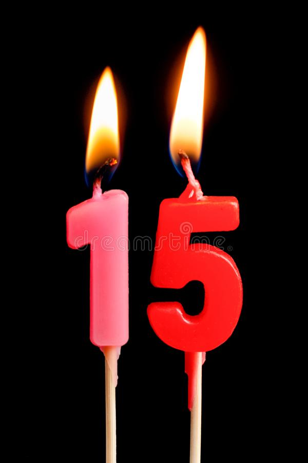 Brennende Kerzen in Form von 15 fünfzehn Darstellungsnummer, Daten für den Kuchen lokalisiert auf schwarzem Hintergrund Das Konze lizenzfreie stockfotografie