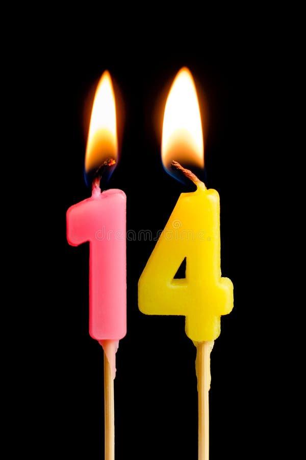Brennende Kerzen in Form von 14 vierzehn Darstellungsnummer, Daten für den Kuchen lokalisiert auf schwarzem Hintergrund Das Konze stockfotografie