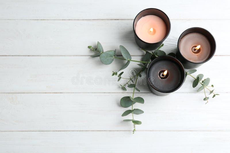Brennende Kerzen und grüne Niederlassungen auf weißem Holztisch, flache Lage stockfotos