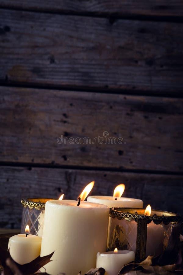 Brennende Kerzen und trocknen Blätter auf Tabelle lizenzfreies stockfoto