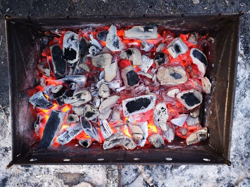 Brennende Kohlen und Brennholz auf dem Grillgitter Vorbereitung der Kohle f?r Grill im offenen Grill Das Konzept von stockfotografie