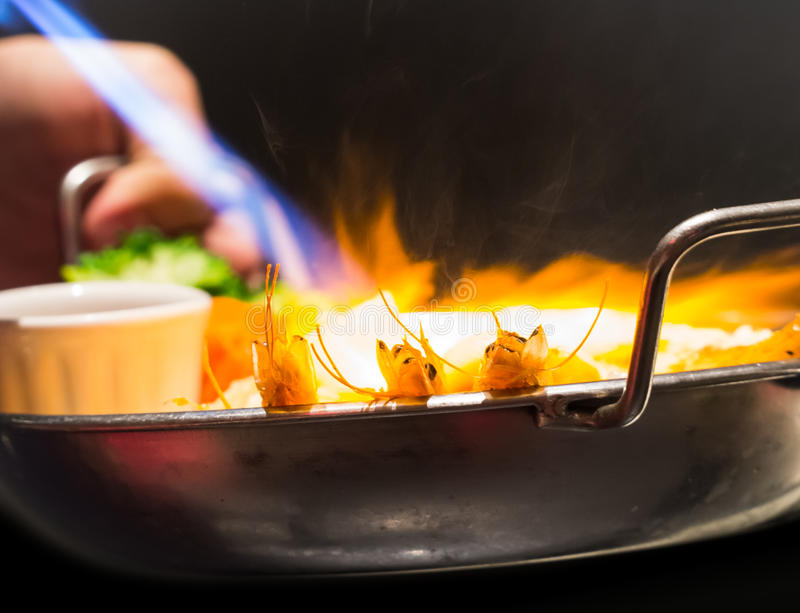 Brennende Meeresfrüchte der heißen Flamme in der Bratpfanne stockfoto