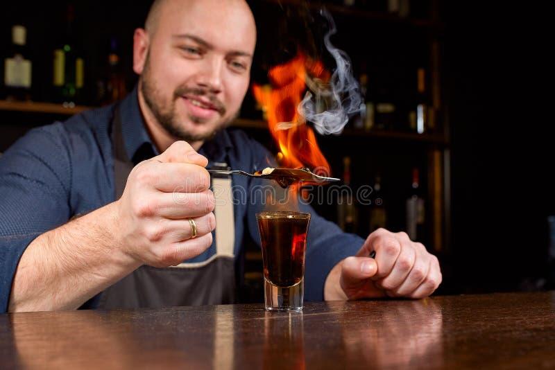 Brennende Show an der Stange Der Barmixer macht heißes alkoholisches Cocktail und zündet Bar an Barmixer bereitet ein brennendes  lizenzfreies stockfoto
