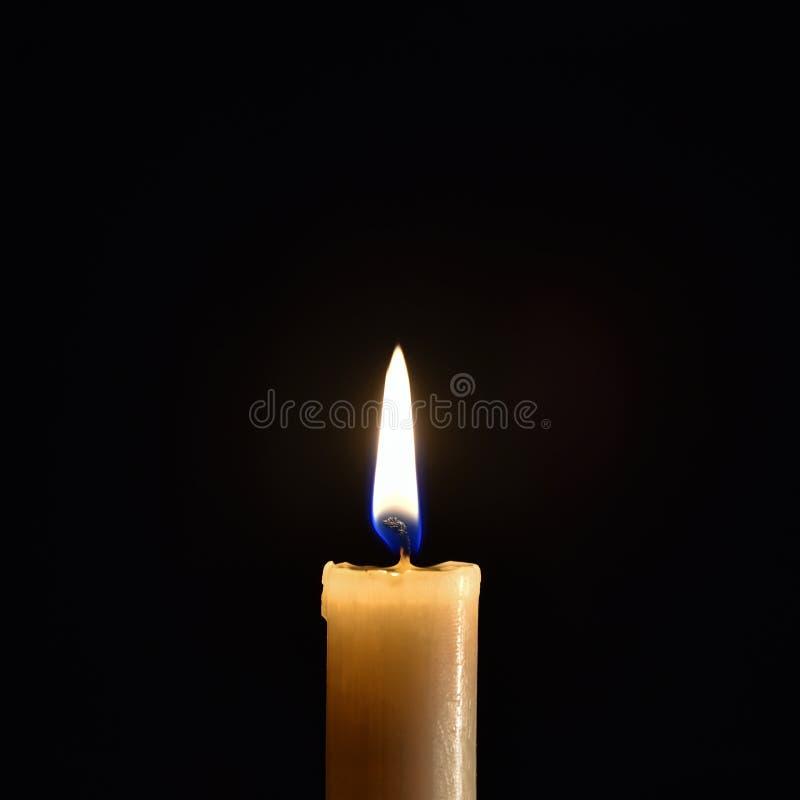 Brennende Wachskerze auf einem schwarzen Hintergrund stockfotos