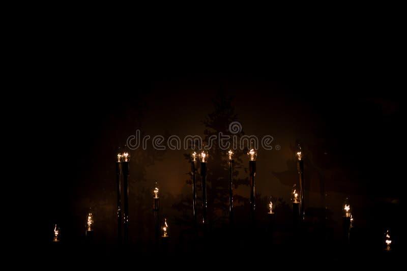 Brennende Wachskerze in der Dunkelheit in der Kirche stockfotografie
