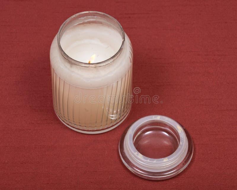 Brennende weiße Kerze im Glasgefäß lizenzfreies stockbild