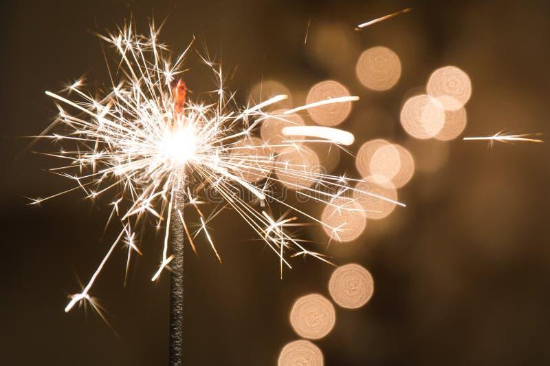 Brennende Wunderkerze steht in einem Glas Dunkler Hintergrund mit defocused mehrfarbigen Lichtern der Girlande lizenzfreies stockbild