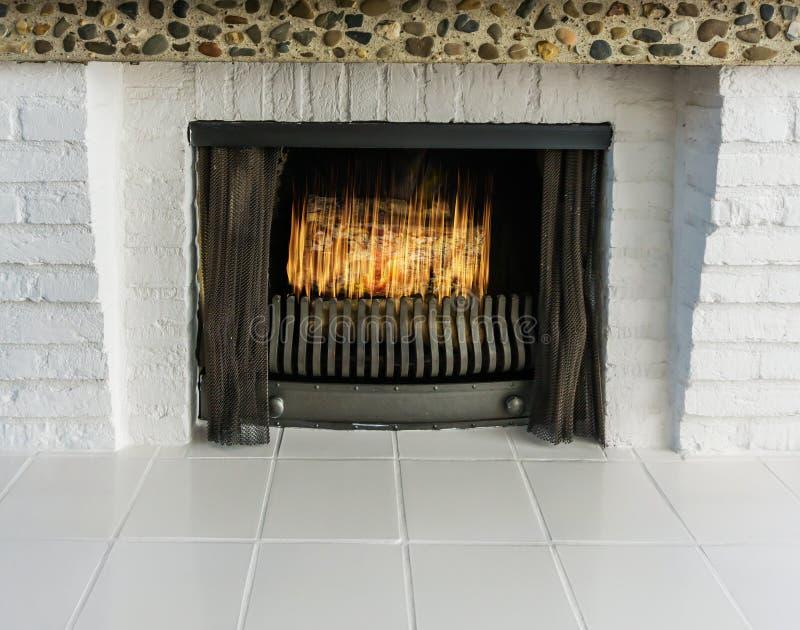 Brennender Feuerplatz mit weißen Ziegelsteinen und weißem Tiling Retrostil aber modernem Blickhintergrund stockfoto