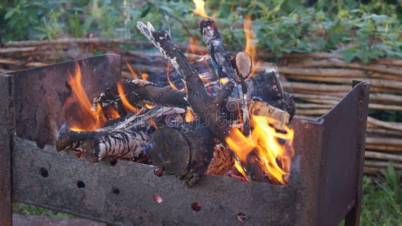 Brennender Holz-, Feuer- und Rauchgrill auf dem Hintergrund des Zauns und des Grases lizenzfreie stockbilder