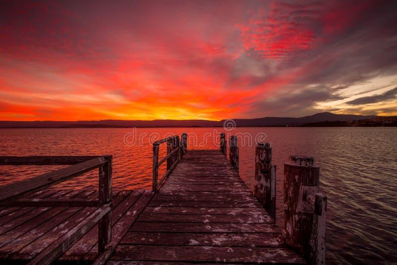 Brennender roter Sonnenuntergang auf dem See mit Bauholzanlegestelle lizenzfreies stockfoto