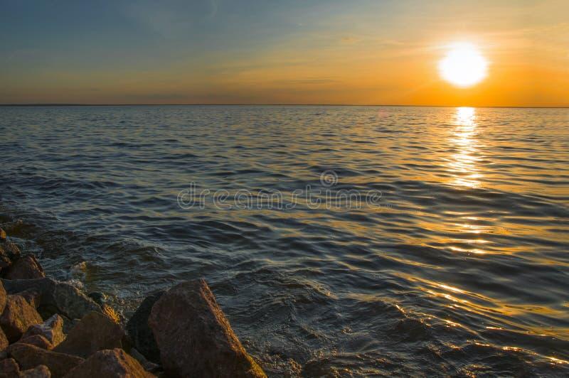 Brennender Sonnenuntergang über dem Meer mit Ufersteinen lizenzfreies stockfoto