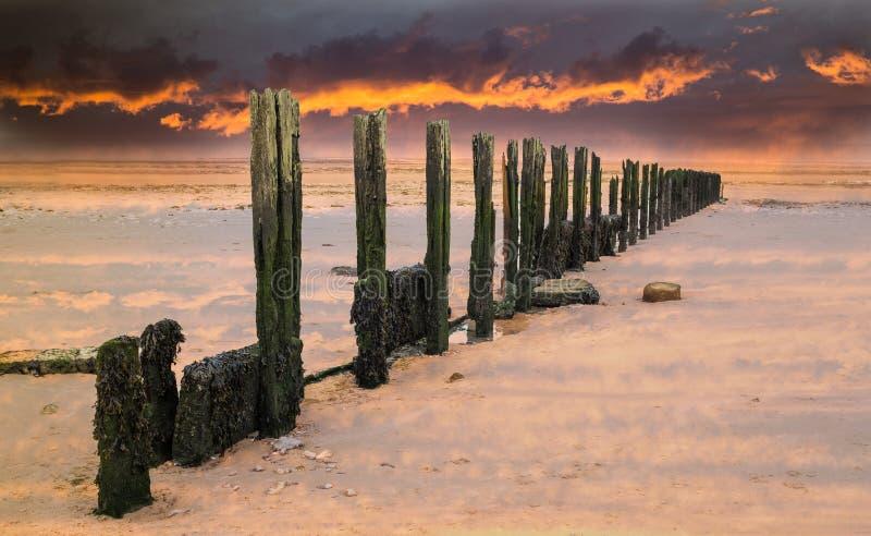 Brennender Sonnenunterganghimmel über altem Wasserunterbrecher, Buhne auf einem nassen sandigen b lizenzfreie stockfotos