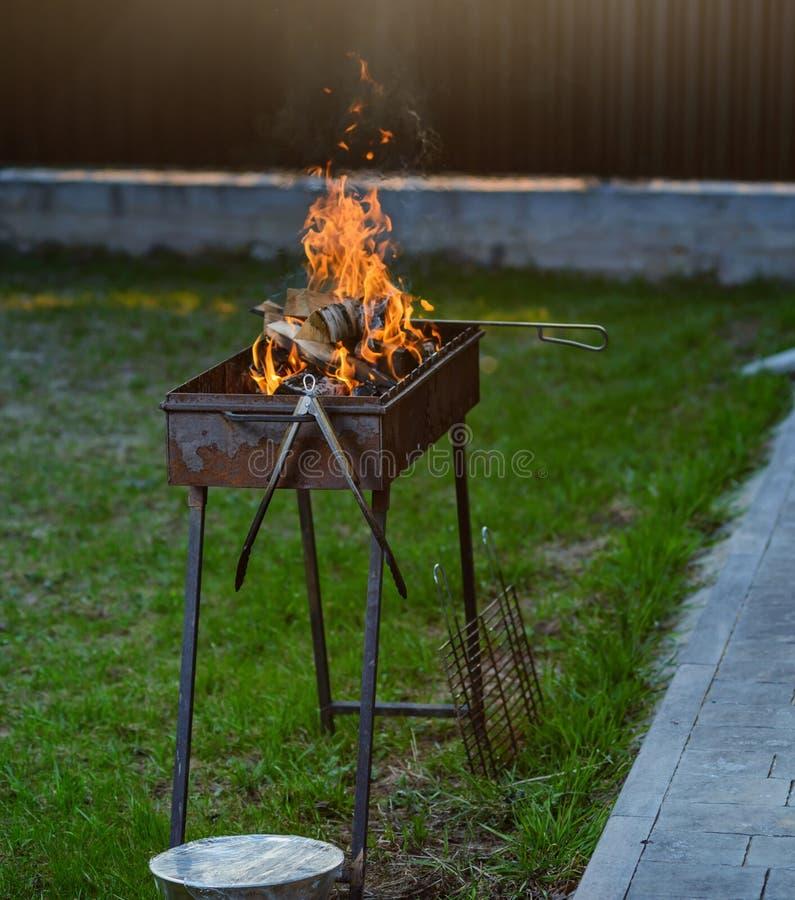 Brennendes Holz im Grill, Rauch vom Feuer auf dem Hintergrund des gr?nen Grases und die Gl?ttungssonne lizenzfreie stockbilder