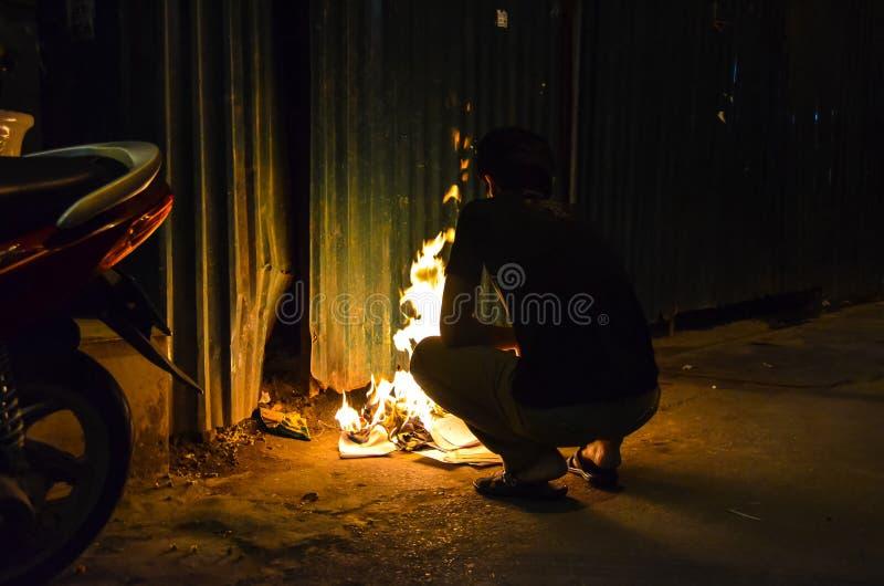 Brennendes Papier des vietnamesischen Kerls nachts stockfoto