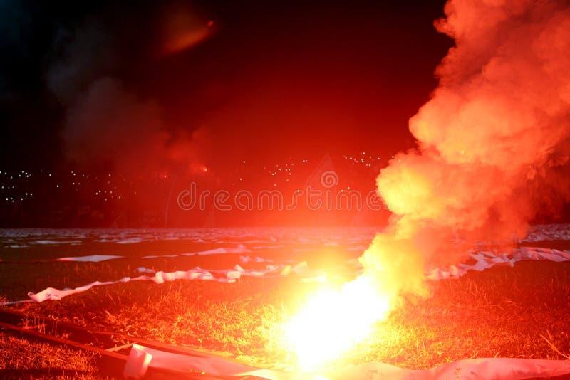 Brennendes rotes Aufflackern, Flamme, Hooligan Fußballfane leuchteten den Lichtern und den Rauchbomben auf dem Fußballplatz Brenn stockbilder