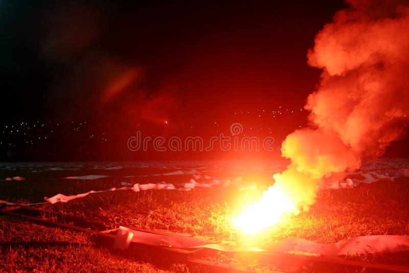 Brennendes rotes Aufflackern, Flamme, Hooligan Fußballfane leuchteten den Lichtern und den Rauchbomben auf dem Fußballplatz Brenn lizenzfreie stockbilder
